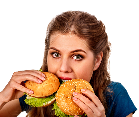 school cafeteria: Woman eating two hamburgers.