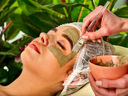 Mud facial mask of woman in spa salon.