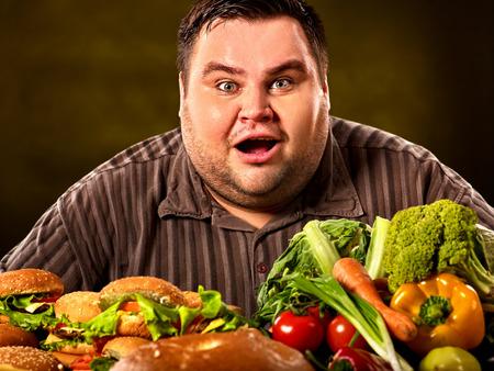 L'uomo grasso che fa la scelta tra alimenti sani e non sani. Archivio Fotografico - 82761700