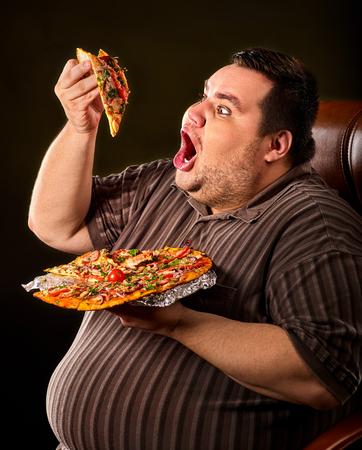 hombre gordo comer pizza de comida rápida en la placa. Foto de archivo