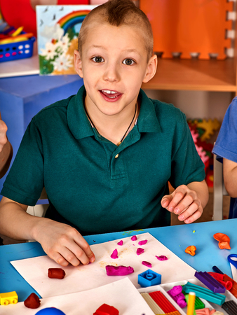 Boy makes animals from colored clay. Stock Photo