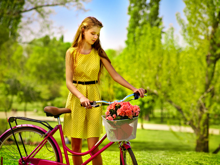 Bikes bicycle girl. Teenager girl wearing yellow polka dots dress looking dreamily keeps bicycle with flowers basket. Romantic style. Happy and free girl teenager on a green glade.