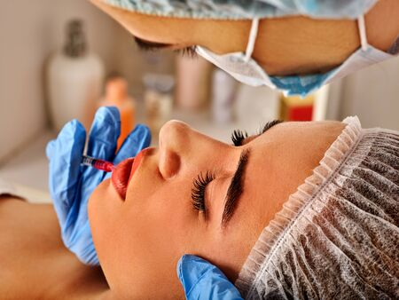 Filler injection for female forehead face. Cropped shot of doctor in medical gloves with syringe injects lips augmentation. Plastic surgery is progressing.