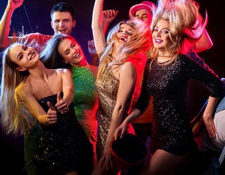 Dance party with group people dancing. Women and men have fun in night club. Happy girl with tousled hair. Back light on girls hair. Rest after hard working week. Stock Photo