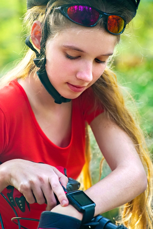 Woman traveling bicycle in summer park. Bicyclist girl watch on smart watch. Girl counts pulse after sport training. Sportswoman waiting for her friends. School trip. Stock Photo