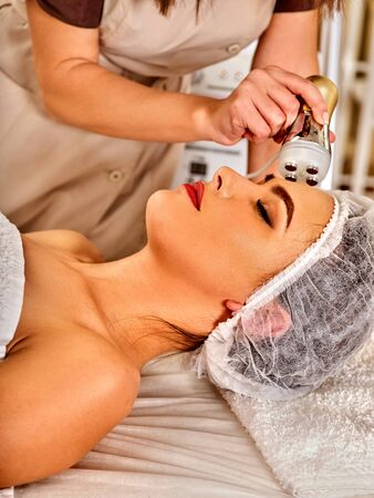 Woman massage beauty salon. Electric stimulation female skin care. Professional equipment microcurrent body lift. Anti aging rejuvenation. Receiving electroporation beauty therapy indoor. Stock Photo