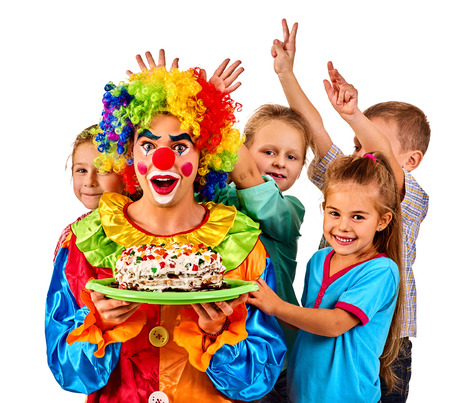 Birthday children clown eating cake with kids together. Celebratory cake on a plate. Fun happy childhood of small group people. Children play with clown.