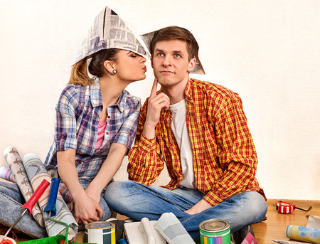 Repair family by happy couple building home using spirit level to measure. Woman and man in newspaper cap renovation apartment. reconciliation after quarrel. Newlyweds kiss in a new apartment.