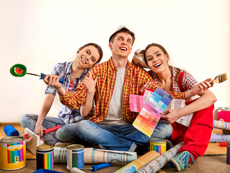 Repair group of people building home using paint roller tools and bank. Women and man in newspaper hat holding color guide renovation apartment. Students took loan for new apartment. Stock Photo