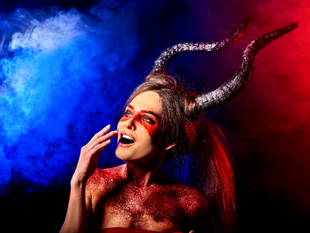 Mad satan woman on black magic ritual of in hell . Witch reincarnation mythical creature on Sabbath. Devil absorbing soul Halloween. Astral beings are among us. Make-up for night club.