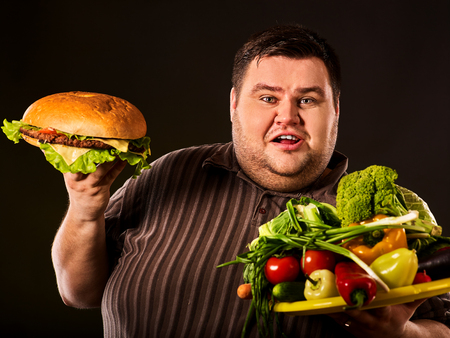 tummy time: Diet fat man who makes choice between healthy and unhealthy food . Overweight male with hamburgers and vegetables trays trying to lose weight first time on black background. Treatment of constipation.