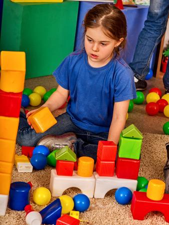 Children building blocks in kindergarten. Group kids playing toy on floor. Top view of interior preschool. Kid is keen on playing dice. Logical constructor.