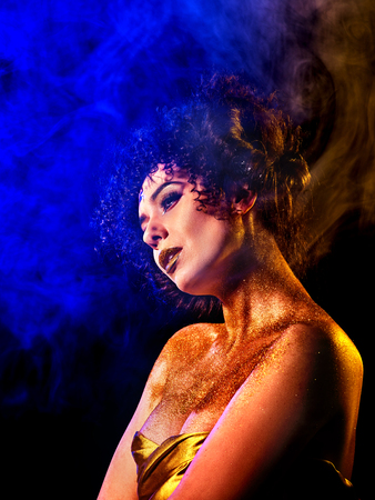 hallucinations: Golden powder cosmetics on bare woman shoulders with decorative. Girl with curls on dark background. Woman at disco in gold mystical fog. Smoke from hookah. Exit of the soul from the body. Stock Photo