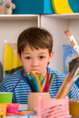 Child boy does study homework tips. Difficulties with homework for school children. Small students painting in art school class. Stock Photo