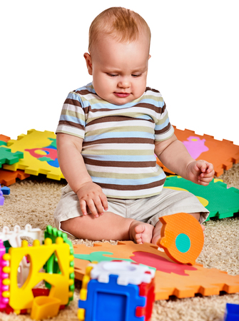 Baby making puzzle. Child jigsaw develops children. Kid holding big pieces and sitting on floor. Portrait of boy playing on soft babys mat in kindergarten. Logical tasks for development of child.