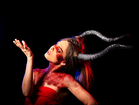hellfire: Mad satan woman on black magic ritual of hell. Witch reincarnation mythical creature Sabbath. Devil absorbing soul Halloween. Astral travel. Make-up for night club for demon inflicts damage. Stock Photo