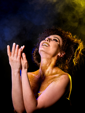 Golden powder cosmetics on bare woman shoulders with decorative. Girl with curls on dark background. Woman at disco In gold mystical fog. Visions of drug addict. Witch going to Sabbath Astral entities