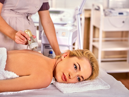 Skin resurfacing body procedure on gold ultrasound face machine. Woman receiving electric lift body massage at spa salon. The best spa salon. Modern technologies and methods rejuvenation.