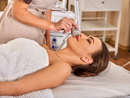 Skin resurfacing facial procedure on gold ultrasound face machine. Female acne treatment. Woman receiving electric lift massage at spa salon. Electronic stimulation female muscles. The best spa salon.