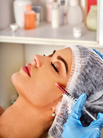 Filler injection for female forehead face. Plastic aesthetic facial surgery in beauty clinic. Botox injections. Doctor in medical gloves with red syringe injects cheeks drug.