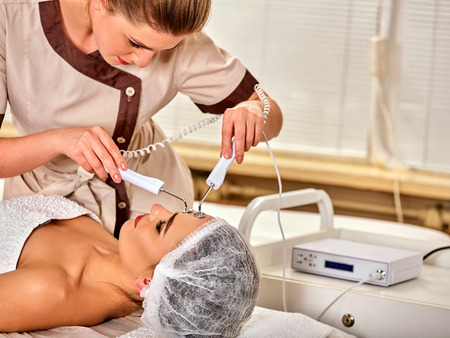 specials: Facial massage at beauty salon. Electric stimulation skin care of woman. Equipment for microcurrent lift face. Anti aging face and neck and close up rejuvenation. The best spa salon. Stock Photo
