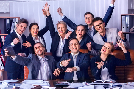 Business people office life of team people are happy with hand up sitting table. Revenue exceeded expenditures for year. People in suits glad with successful deal and celebrate success in office. Stock Photo