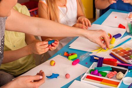 Plasticine modeling clay in children class. Teacher teaches kids together play dough and mold from plasticine in kindergarten or preschool. Group of four people. They learn to live in a team.