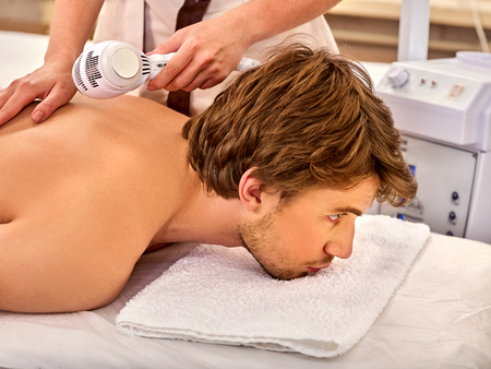 Ultrasonic body treatment on ultrasound skin care machine. Man receiving electric lift massage at spa salon. Electronic stimulation he muscles. The best spa salon. Stock Photo