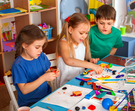 Child dough play in school. Plasticine for children. mold from plasticine in kindergarten. Kids knead modeling clay with hands in preschool. Zoo from plasticine. They learn to live in a team.