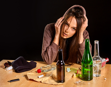 Woman alcoholism is social problem. Female drinking is cause of nervous stress. She in hood with rroup of green alcohol bottle in bad mood. Gap between a guy and a girl.