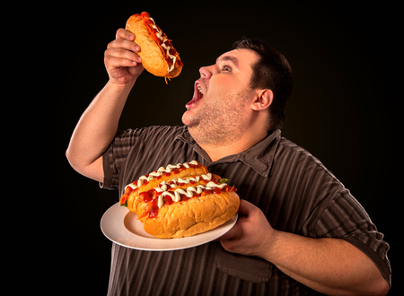 enraged: Diet failure of fat man eating fast food hot dog on plate. Breakfast for overweight person who greedily eats lot. Use of semi-finished products for food. Enraged by large amount of food fat.