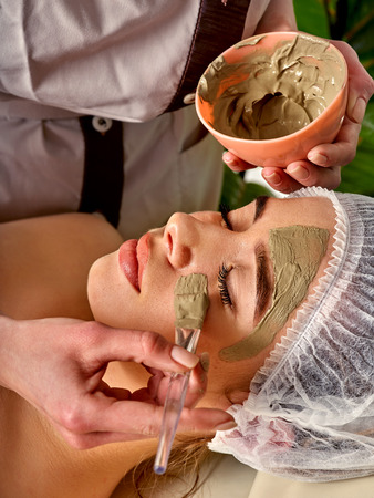 Mud facial mask of woman in spa salon. Massage with clay full face. Girl on with therapy room. Beautician with bowl therapeutic procedure isolated background. Skin softening. Stock Photo