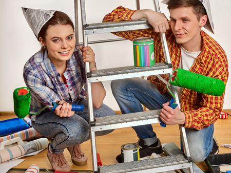 Repair family by happy couple building home using ladder. Woman and man in newspaper cap renovation apartment. Profitable loan for repairs.