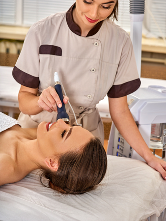 Ultrasonic facial treatment on ultrasound face machine. Woman with nude shoulders electric lift massage spa salon. Electronic stimulation female muscles. The best spa salon. Stock Photo
