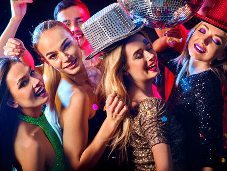 Dance party with group people dancing. Women and men have fun in night club. Happy girl with tousled hair . Back light on girls hair. Rest after a hard day at work.