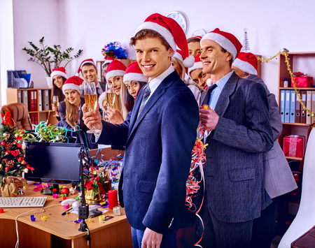 Christmas business cocktail party in office. Xmas corporate with group people in holiday hat drinking champagne.