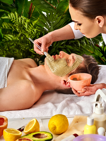 Mud facial mask of man in spa salon. Massage with clay face. Facelift. Apply mask on face with brush. Beautician with bowl therapeutic procedure. Still life with lemons in foreground. Stock Photo