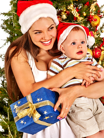 Christmas family with gift box under holiday tree. Mother and baby in Xmas hat on home party on isolated.