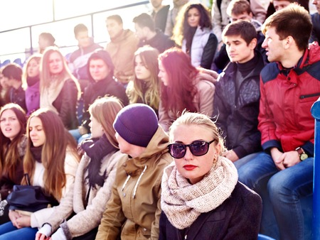 Fans cheering in stadium. Group people wait your favorite team and worry on tribunes. Youth support your favorite team. Blonde with glasses in foreground.