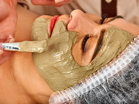 Collagen face mask. Facial skin treatment. Face of woman of elderly woman 50-60 years old receiving cosmetic procedure in beauty salon close up. Professional cosmetologist.