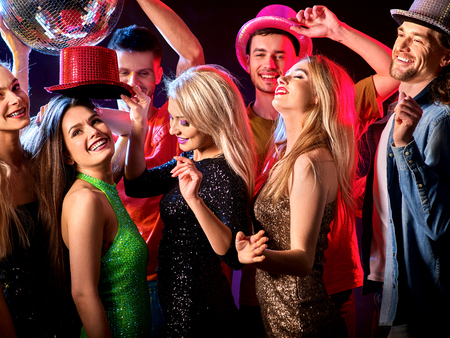 Dance party with group people dancing. Women and men have fun in night club. Happy girl with tousled hair. Rest after a hard day at work.. People in brilliant suits dance under influence of alcohol. Stock Photo