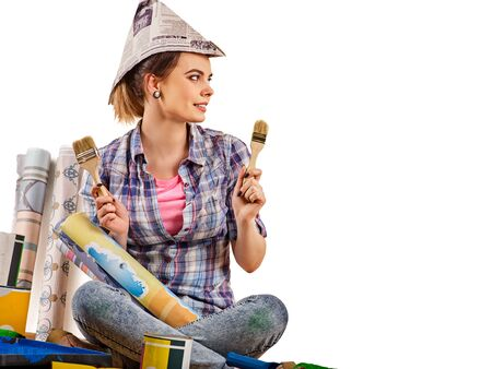 Repair home woman holding paint brush for wallpaper. Female in newspaper cap renovation apartment. Paint bank and roll paper background. Student earns extra money at construction site. Stock Photo