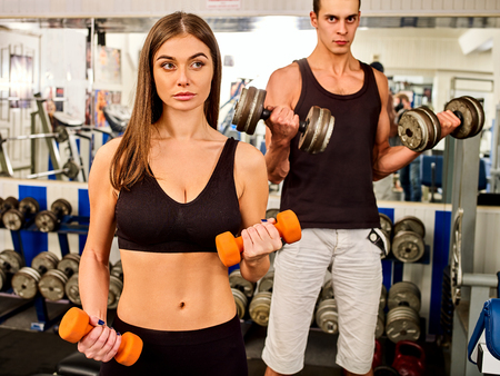 Woman holding dumbbell workout at gym. Cropped shot of of middle section of bare belly. Friends men on background. Body that you want concept. loving couple trains together.