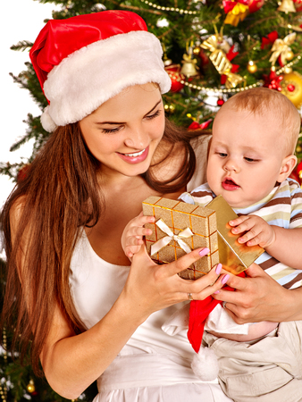 Christmas family with gift box under holiday tree. Mother and baby in Xmas hat on home party on isolated. New Year discounts for childrens products.