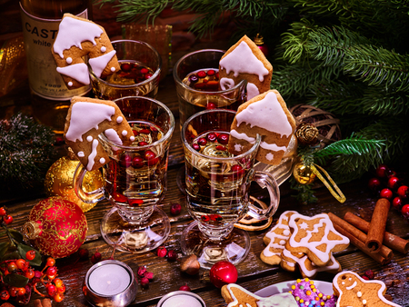 Christmas table decorations with glasses of punch and gingerbread cookies, bottle of wine in background. Xmas arrangement top view.