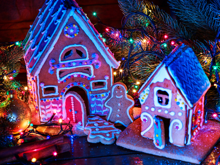 Ginger bread houses with Christmas garland. Xmas food gingerbread man cookies decorating holiday village table with burning candles. Gingerbread tree lies on table. Archivio Fotografico
