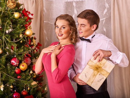 Couple on party near Christmas tree take gift box and Xmas presents. Happy family on holiday. Stock Photo