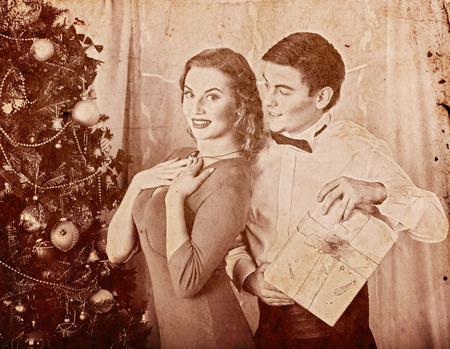 Christmas nostalgy couple on party near Xmas tree take gift box. Happy family on holiday. Vintage sepia old retro photo 1910-1940. Stock Photo