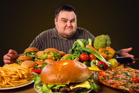 Diet fat man who makes choice between healthy and unhealthy food. Overweight male with hamburgers, french fries and vegetables trays trying to lose weight first time. Salaries are enough for all needs