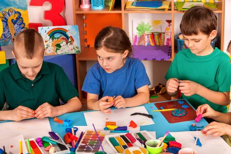Child dough play in school. Plasticine for children. mold from plasticine in kindergarten. Kids knead modeling clay with hands in preschool. Newcomer in a childrens team.